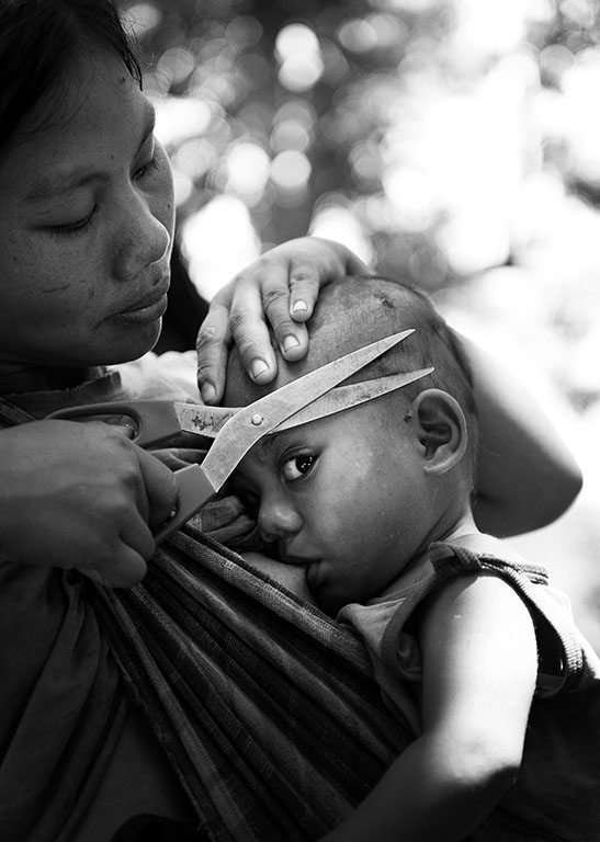 A mother gives her baby a haircut and feed at the same time. Luangprabang, Northern Laos Tour.