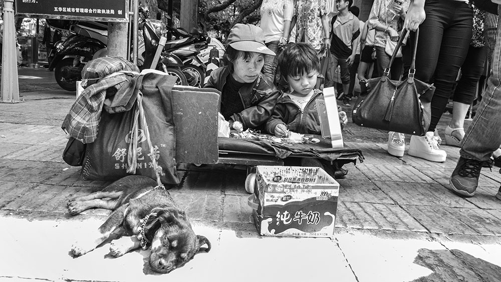 A Mother & Child Selling Their Goods On The Streets Of Kunming-China. Tours also available here too.